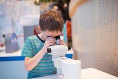 Pojke för litet barn som ser till och med mikroskopet royaltyfri foto