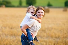 Pojke för moderinnehavunge på armar på vetefält i sommar arkivbilder
