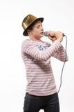 Pojke för sångarebrunetttonåring i en rosa ärmlös tröja i guld- hatt med en mikrofon Arkivfoto