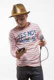 Pojke för sångarebrunetttonåring i en rosa ärmlös tröja i guld- hatt med en mikrofon Royaltyfri Fotografi