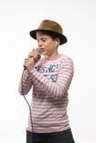 Pojke för sångarebrunetttonåring i en rosa ärmlös tröja i guld- hatt med en mikrofon Arkivbild