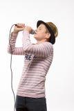 Pojke för sångarebrunetttonåring i en rosa ärmlös tröja i guld- hatt med en mikrofon Royaltyfria Foton