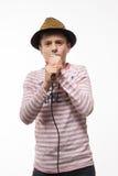 Pojke för sångarebrunetttonåring i en rosa ärmlös tröja i guld- hatt med en mikrofon Royaltyfri Bild
