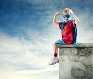 Pojke för toppen hjälte med lyftta nävar Arkivbilder