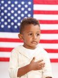 Pojke framme av amerikanska flaggan med handen över hjärta Arkivbild