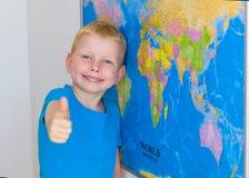 Pojke framme av amerikanska flaggan med tummar upp Arkivfoto