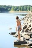 Pojke hållande ögonen på sjö Arkivbild