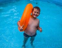 Pojke i att ha gyckel i simbassängen Royaltyfria Foton