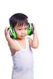 Pojke i bärande öronskydd för en vit singlet Arkivfoton