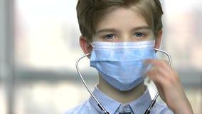 Pojke i blå medicinsk maskering arkivfilmer