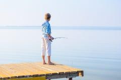 Pojke i blått skjortaanseende på en paj Royaltyfri Foto