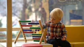 Pojke i dagiset som spelar med kulrammet stock video