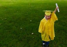 Pojke i den gula förskole- avläggande av examenkappan som upp rymmer hans diplom arkivbild