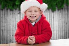 Pojke i den santa hatten som ler på kameran Arkivfoto