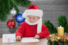 Pojke i den santa hatten som skrivar ett brev Royaltyfri Bild
