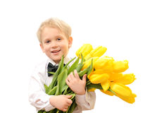 Pojke i den vita skjortan med buketten av gula tulpan Arkivbild