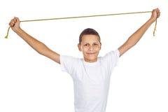 Pojke i den vita T-tröja som streching det guld- repet Royaltyfria Bilder