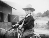 Pojke i en cowboyhatt på en häst (alla visade personer inte är längre uppehälle, och inget gods finns Leverantörgarantier som där Royaltyfria Bilder