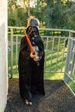 Pojke i en dräkt av Darth Vader med svärdet royaltyfria foton