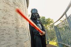 Pojke i en dräkt av Darth Vader med svärdet royaltyfri foto