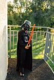 Pojke i en dräkt av Darth Vader med svärdet fotografering för bildbyråer