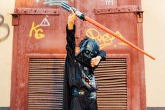 Pojke i en dräkt av Darth Vader med svärdet royaltyfri fotografi