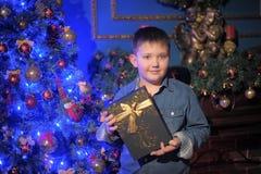 Pojke i en grov bomullstvillskjorta med en gåva i händer Arkivbild
