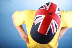 Pojke i en gul t-skjorta som bär ett lock med Union Jack arkivbild