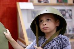 Pojke i en militär hjälm Royaltyfri Foto