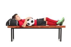 Pojke i en röd fotbollärmlös tröja som ligger på en bänk Royaltyfria Bilder