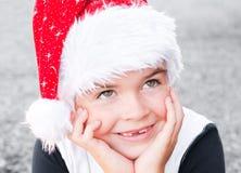 Pojke i en Santa Claus hatt Arkivfoto