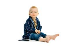 Pojke i ett bandsammanträde på ett vitt golv Arkivbild