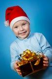 Pojke i ett lock av Santa Claus med gåvor Royaltyfri Foto