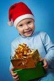 Pojke i ett lock av Santa Claus med gåvor Royaltyfri Fotografi
