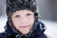 Pojke i ett lock med earflaps Royaltyfri Foto
