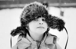 Pojke i ett lock med earflaps Royaltyfria Bilder