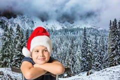 Pojke i ett rött lock av Santa Claus Arkivfoton