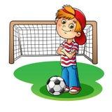 Pojke i ett rött lock och en randig t-skjorta med en fotbollboll och en foo Royaltyfri Bild