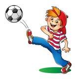 Pojke i ett rött lock som sparkar en fotbollboll Royaltyfri Bild