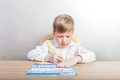 Pojke i ett vitt skjortasammanträde på ett skrivbord och attraktioner i färgläggningen av kulöra blyertspennor på en vit bakgrund arkivbild