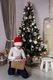 Pojke i för hattöppning för jultomten röda gåvor för jul Arkivfoton