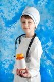Pojke i flaska för doktorsdräktinnehav med preventivpillerar arkivfoton