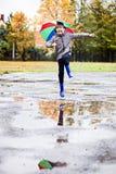 Pojke i gummiblåttrainboots som hoppar för att smutsa ner pöl Royaltyfri Fotografi