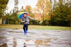 Pojke i gummiblåttrainboots som hoppar för att smutsa ner pöl Fotografering för Bildbyråer