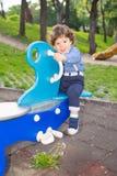 Pojke i gungbrädet som bort ser Royaltyfri Bild