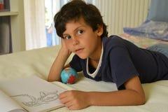 Pojke i hans hållande ögonen på komiker för rum royaltyfria bilder
