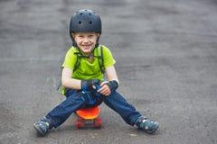 Pojke i hjälmen som poserar med skateboarden Arkivbilder
