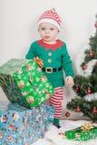 Pojke i julälvadräkt En behandla som ett barn nära en julgran royaltyfri foto