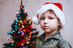 Pojke i jultomten lock på julgranbakgrund arkivbilder