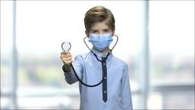 Pojke i kirurgisk maskering genom att använda stetoskopet arkivfilmer